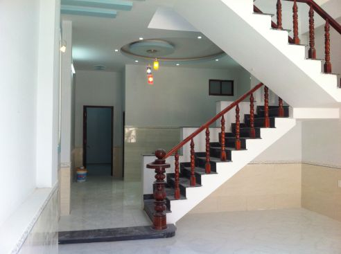 Trung tâm nhà có cầu thang đúc tay vịn bằng gỗ.