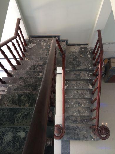 Cầu thang đúc tay vịn bằng gỗ, bậc thang lát đá hoa cương.
